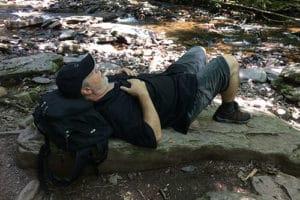 husband napping on rock at Rickett's Glen