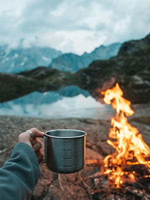 camper holding a mug by a fire and lake