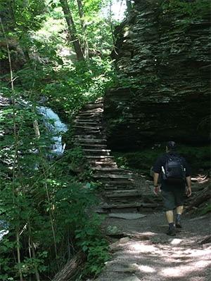 man hiking rickett's glen state park falls trail